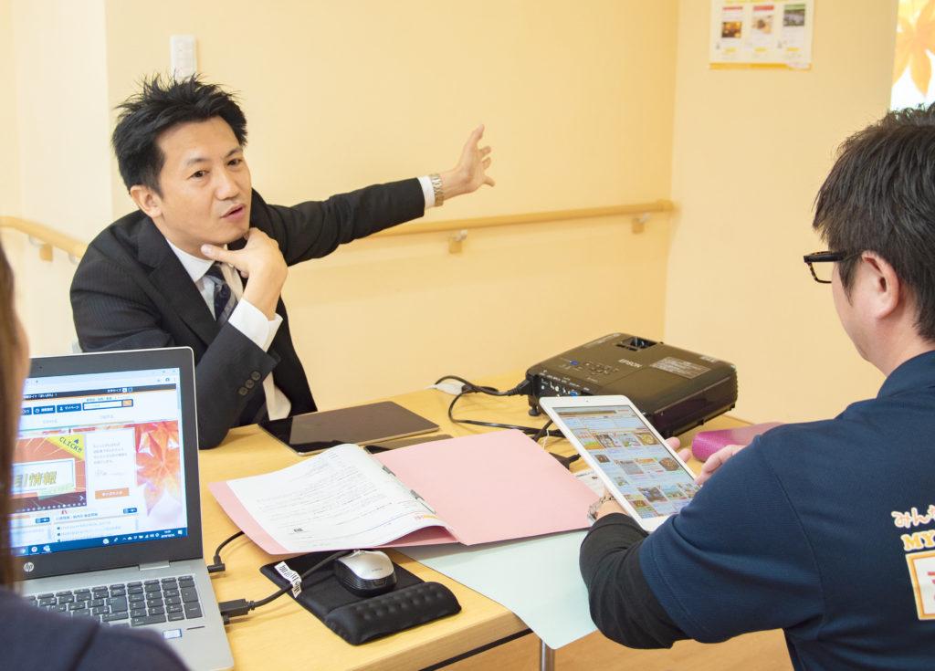 スタッフの方々とミーティングをする岩村社長